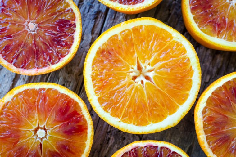 Sliced blood oranges texture. Citrus background. Cut ripe juicy Sicilian Blood oranges fruits on old wooden background. Top view.