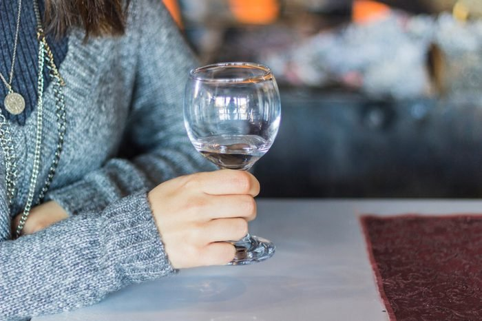 Shot for woman holds empty wine glass with blurry background in Izmir at Turkey for winter seasonShot for woman holds empty wine glass with blurry background in Izmir at Turkey for winter season