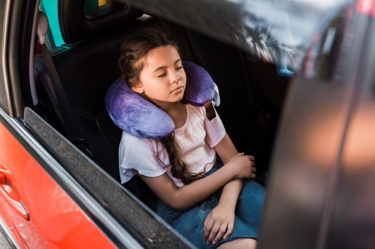 adorable kid sleeping in car with neck pillow