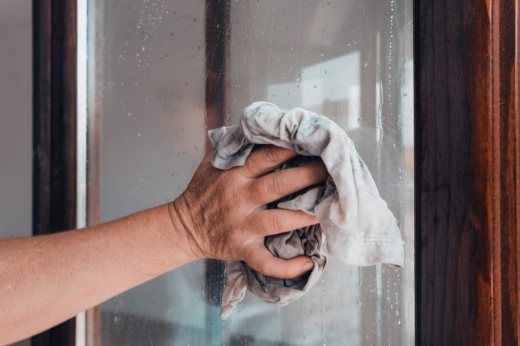 woman hand with old rag cleaning window