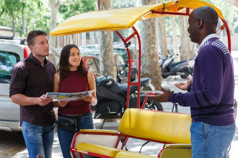 Pretty girl with boyfriend traveling on rickshaw through city streets, friendly talking with driver