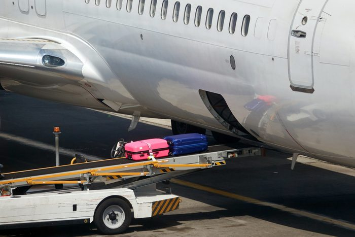 Loading suitcases of tourists in the plane.