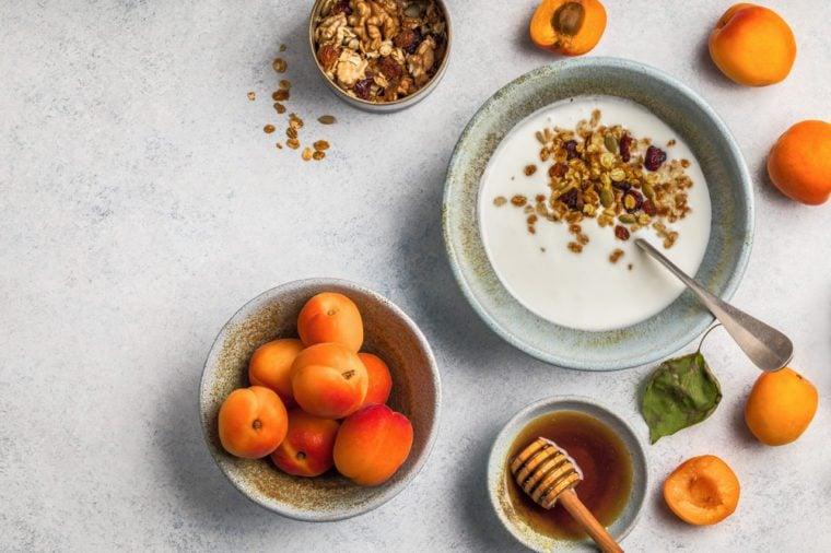 Healthy breakfast with yogurt, honey granola, fresh apricots. Flat lay, top view.