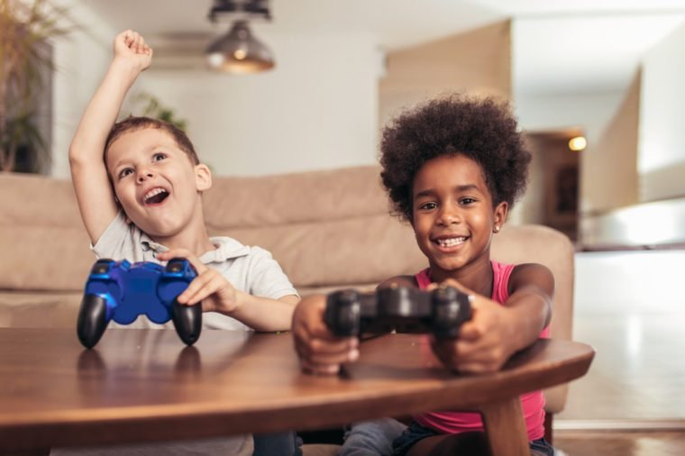 Boy and girl sitting in living room playing video game together