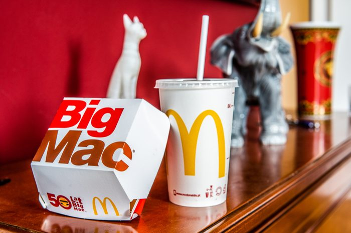 Warsaw, Poland, July 22, 2018 McDonald's Big Mac with two 100% pure beef patties and sauce sandwiched between sesame seed bun, with refreshing Coca-Cola Coke, big yellow McDonald's M sign, logo on cup