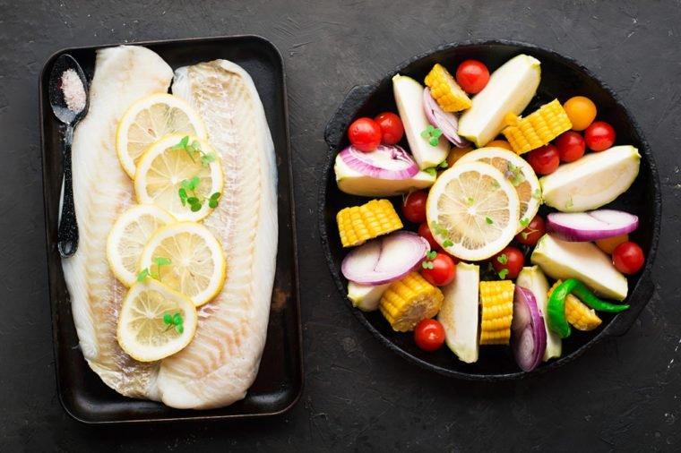 Two dishes before baking: cod with lemons and assorted organic garden vegetables in round form: corn, zucchini, onion, tomatoes, herbs. Top View
