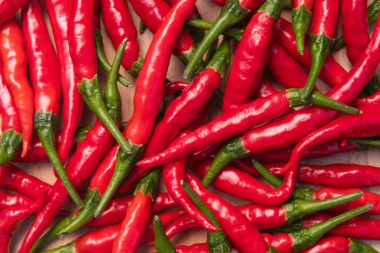 Fresh red hot thai chili peppers on wooden surface