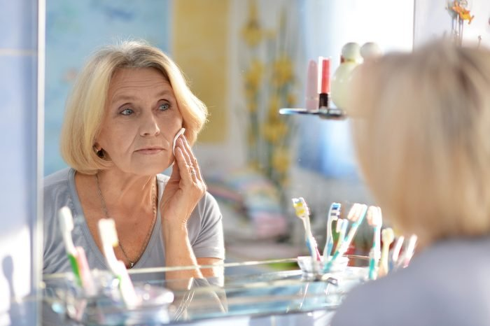 beautiful elderly woman doing make-up in the bathroom