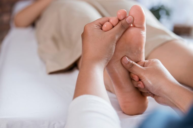 portrait of therapist giving relaxing reflexology Thai leg massage treatment to a woman in spa