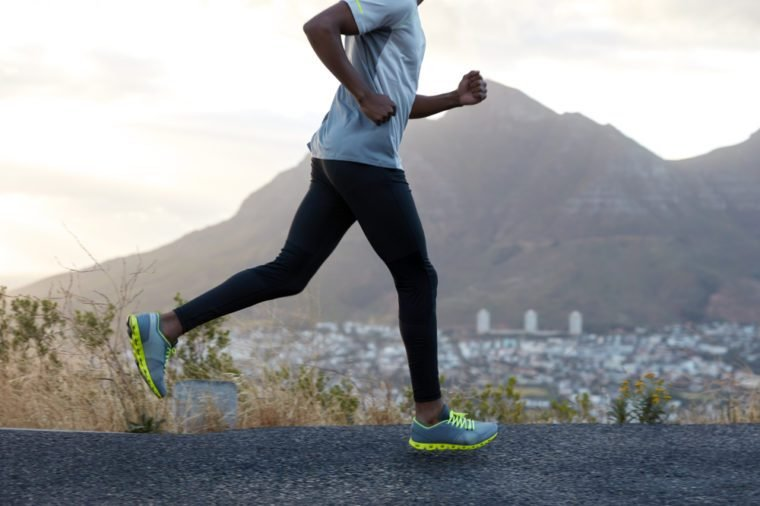 Healthy dark skinned man in action, runs along road near mountains, wears comfortable sneakers, casual clothes, has sporty body. Fast male athlete poses against sky background. Racing competition