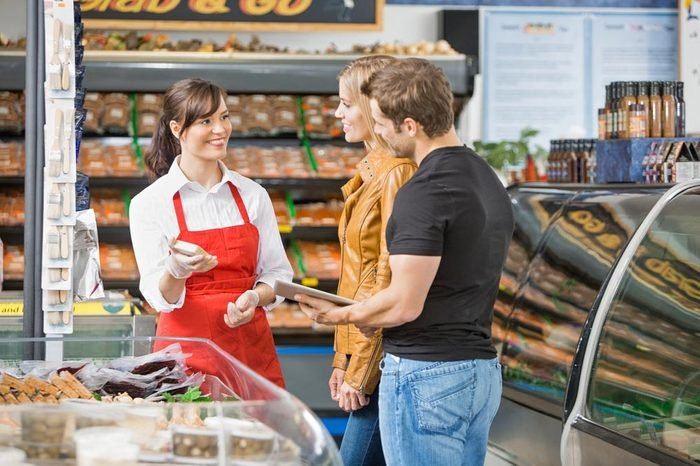 Smiling saleswoman assisting couple in buying meat at butcher's shop