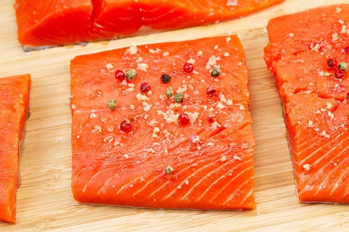 Closeup horizontal photo of dried red peppercorns and sea salt on top of fresh Wild Red Salmon pieces with natural bamboo cutting board underneath