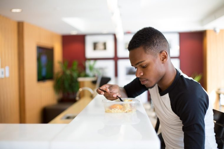 Closeup portrait young handsome man eating noodles, sitting at white table, isolated luxurious, urban indoor background