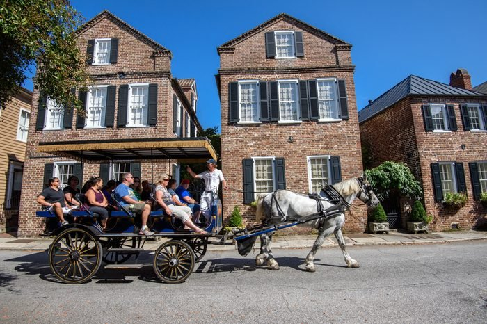 CHARLESTON, SC, USA -OCTOBER 13: Horse carriage with tourists enjoying facades of Societe Francaise on October 13, 2014 in Charleston, SC. Historic architecture attracts tourists to Charleston,SC..