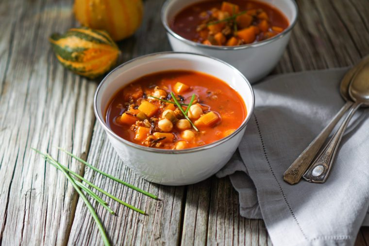 Vegetarian tasty spicy chili chick pea pumpkin wild rice soup pozole stew bowl on a wooden background