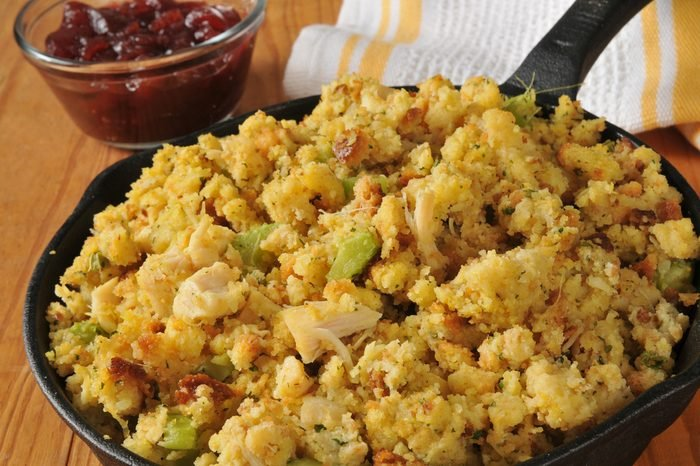Cornbread stuffing in a cast iron skillet with cranberry sauce