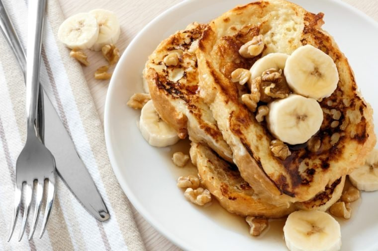 Plate of delicious French toast with bananas, walnuts and dripping maple syrup, overhead view