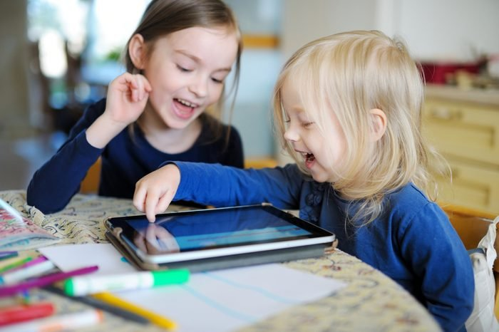 Two adorable little sisters playing with a digital tablet at home