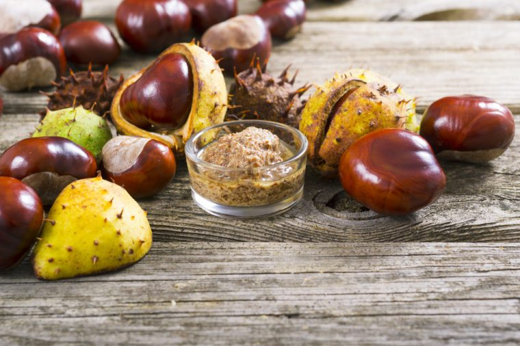 medicine and cosmetics raw ingredient: alcohol tincture from horse chestnuts on old wood table background