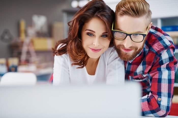 Closeup of happy couple looking at laptop