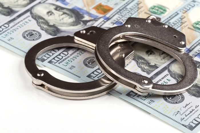 handcuffs on dollar banknotes background