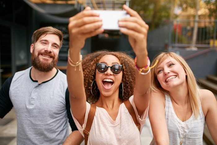Group of smiling friends taking selfie with mobile phone. Multiracial man and women enjoying themselves outdoors and taking pictures with smart phone.