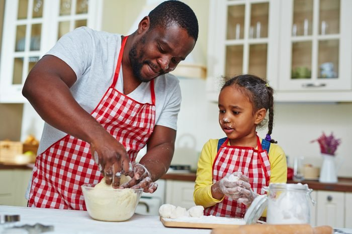 Young man and his daughter making pastry in the kitchen