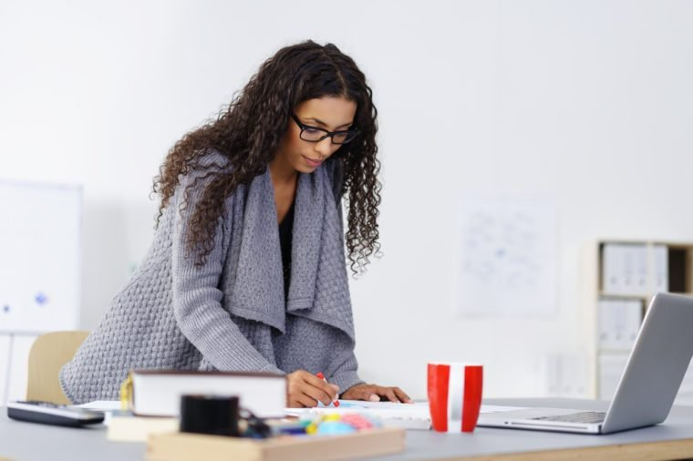 Young African American design artist at work in her studio standing at her table sketching on a pad with colored crayons