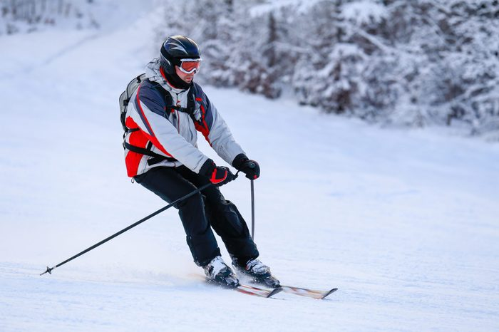Skier skiing downhill in winter mountains