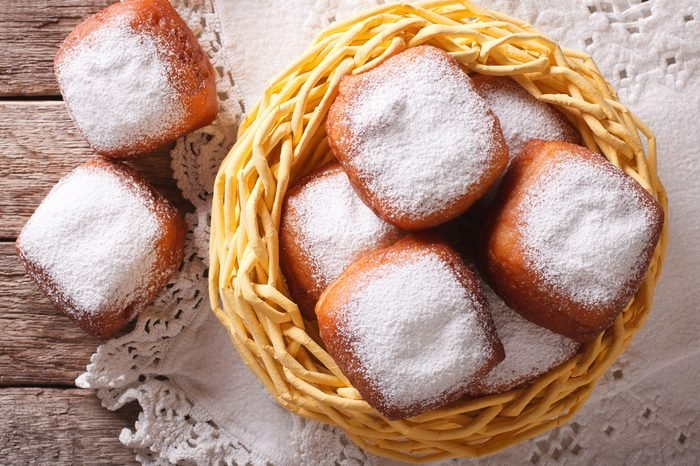 French beignets donuts with powdered sugar close-up on the table. horizontal view from above