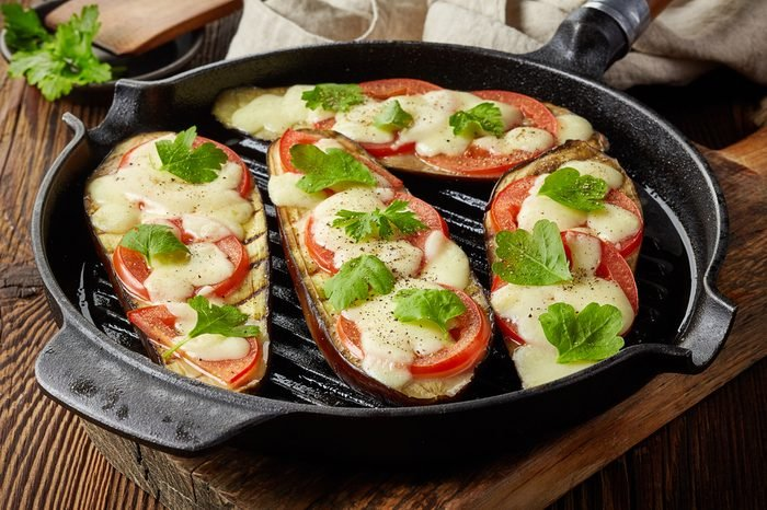 grilled eggplants with tomato and cheese on cooking pan