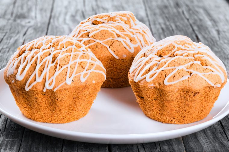 Delicious Homemade Whole Wheat muffins with raisins, nuts and ginger on a white dish, close-up