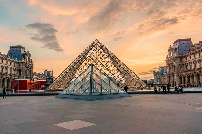 View of famous Louvre Museum with Louvre Pyramid at evening. Louvre Museum is one of the largest and most visited museums worldwide.