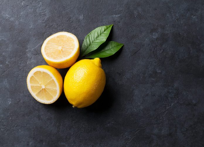Fresh ripe lemons on dark stone background. Top view with copy space