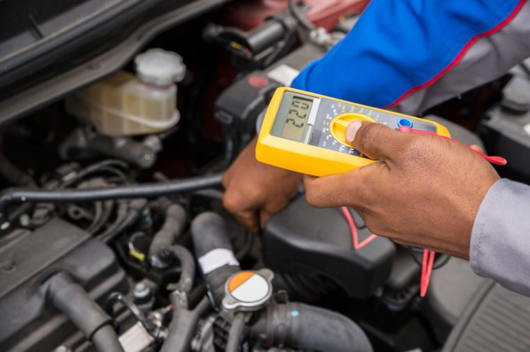 Close-up Of Mechanic Checking A Car Battery Level With Multimeter