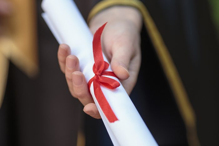 Students graduate holding a diploma with red ribbon
