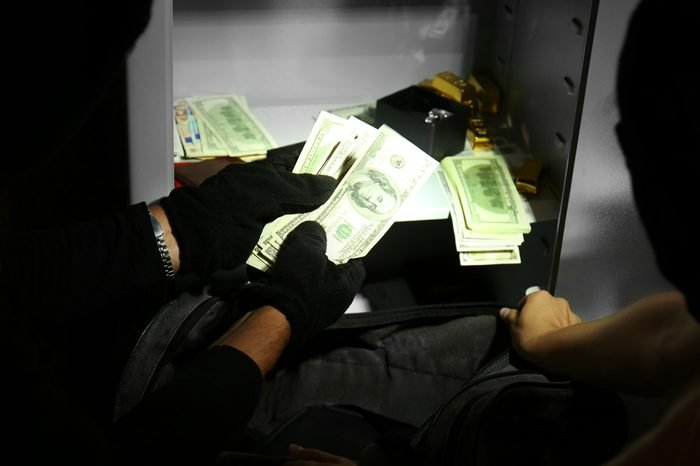 Thieves stealing money from safe