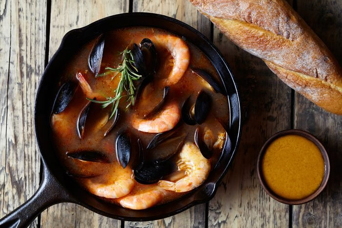 Bouillabaisse seafood fish soup with prawns, mussels tomato, lobster. Sauce Rouille. Traditional Marseille France dish. Rustic style background. Flat lay.