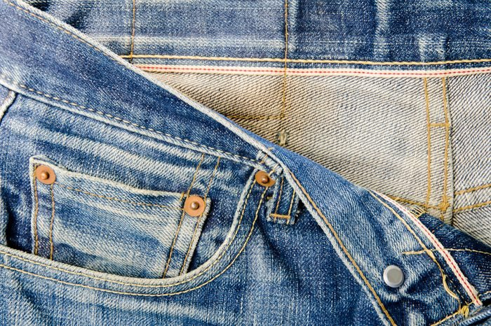 Details of jeans male. The front waist of the pants with red seam.