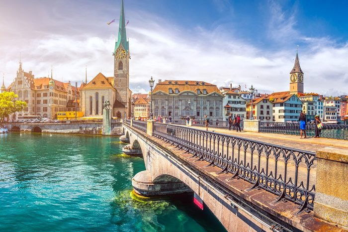 Beautiful view of the historic city center of Zurich with famous Fraumunster Church and swans on river Limmat on a sunny day with blue sky in summer, Canton of Zurich, Switzerland