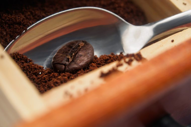 Spoon with coffee bean and grounded coffee. Grounded coffee.