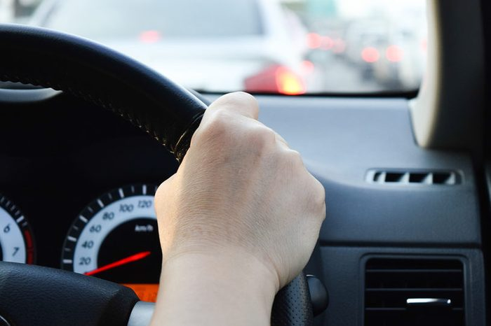 woman driving car, hand hold steering wheel in a traffic jam