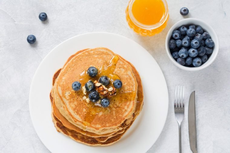 Stack of pancakes with fresh blueberries, nuts and honey on white plate. Healthy breakfast food. Table top view.