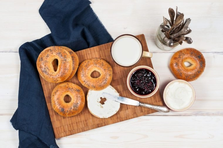 Fresh homemade Poppy bagels bread with cup of milk, cream cheese and berries jam. Top view