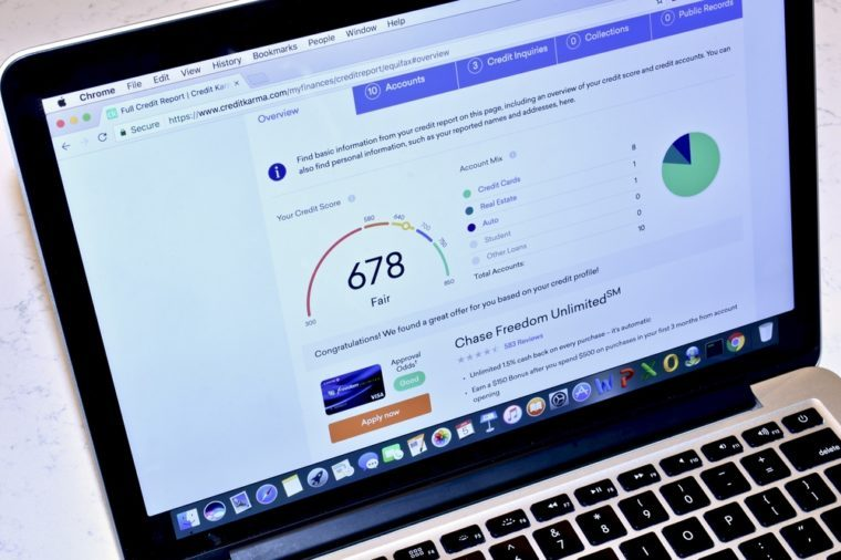 An Apple MacBook Pro displaying the Credit Karma webpage with relevant credit score information.