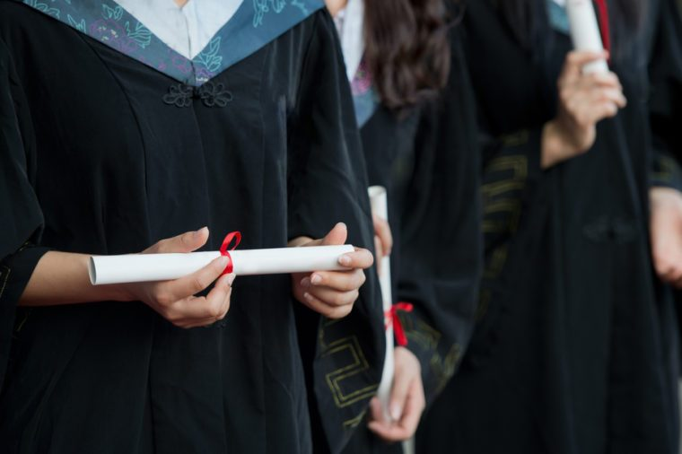 people in a gown holding a diploma.