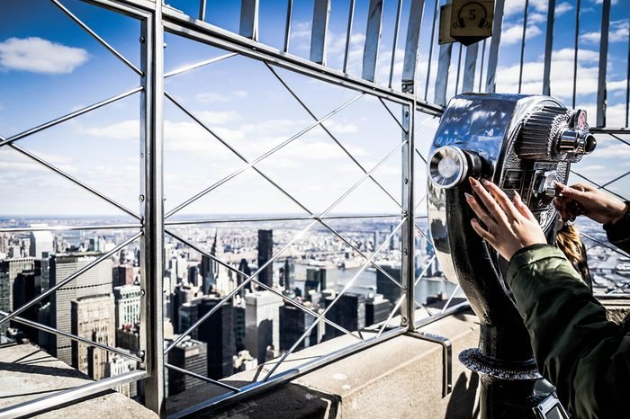 Close up of a girl that looks manhattan by telescope, from the Empire State Building