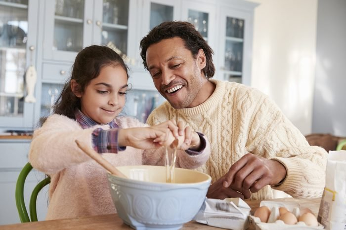 Father And Daughter Baking Cookies At Home Together