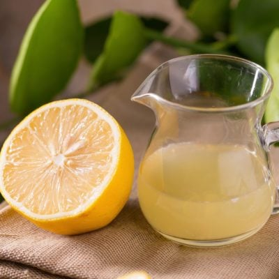 glass bowl of freshly squeezed lemon juice, lemon squeezer and ripe lemons on wooden background.