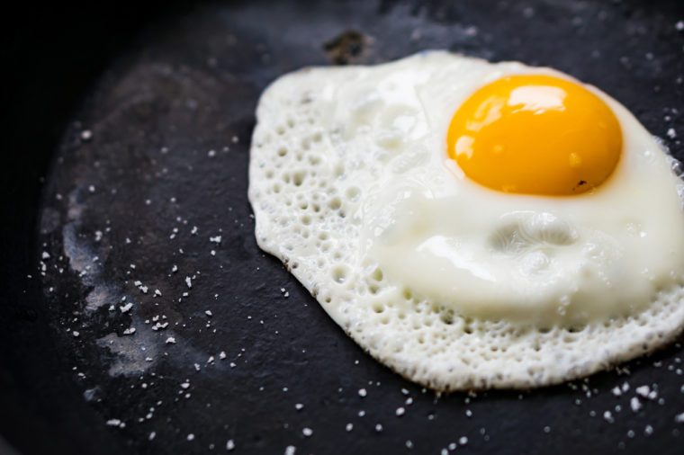 Closeup chips are down egg in a black cast-iron pan, without oil, sprinkled with salt. Concept health.